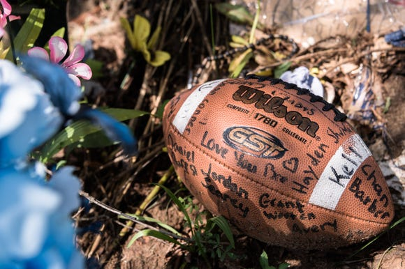 A football left at a vigil at the site where Markell Lipscomb, 17, a rising senior at Polk County high school and a member of the football team, was killed in a car accident in July.