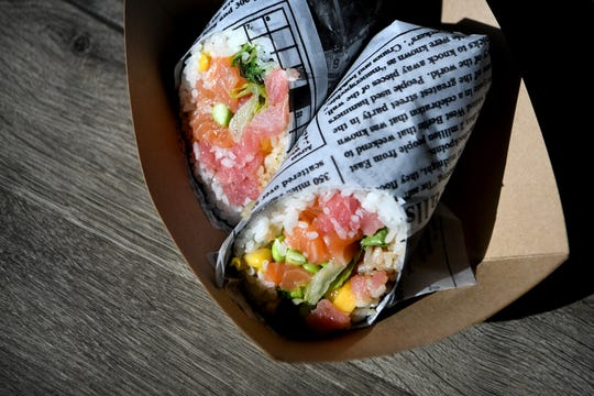 The Yum's Classic sushi burrito at Yum Sushi Burrito and Poke is filled with Ahi tuna, salmon, romaine lettuce, seaweed salad, mango, edamame, sweet corn and topped with sriracha aioli and eel sauce.