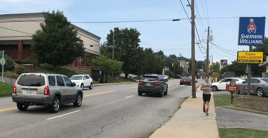 A runner heads south on a stretch of Merrimon Avenue that the state Department of Transportation has considered widening.