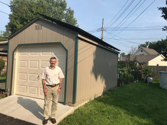 Terry Woodnorth by his detached garage that supports a portion of his rooftop solar array supply much of his energy needs throughout the year.