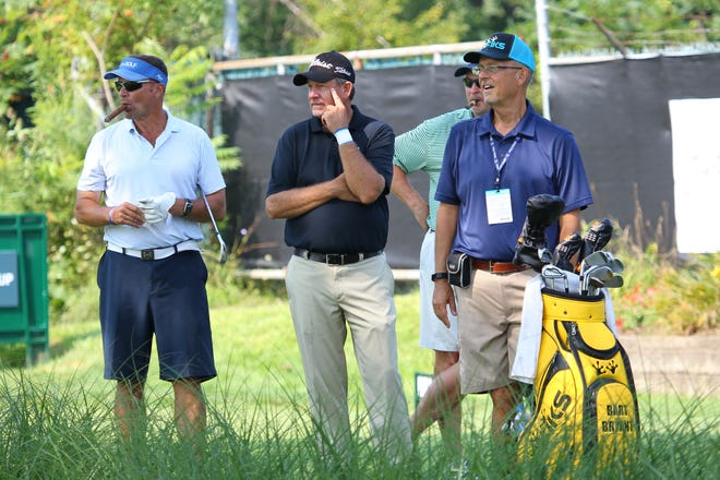 Bart Byrant and his group watch the previous green while waiting to tee off.