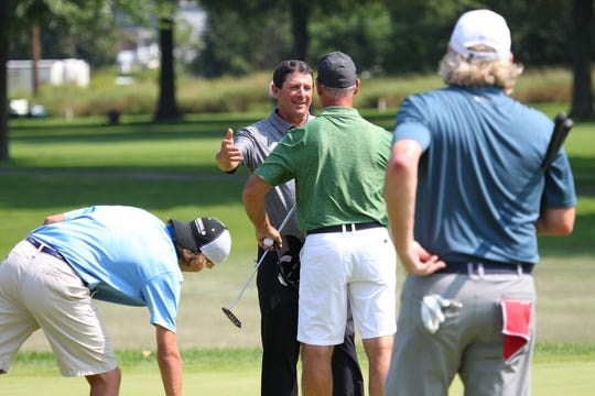 Billy Andrade congratulates Chris Quinn after a great putt on 13