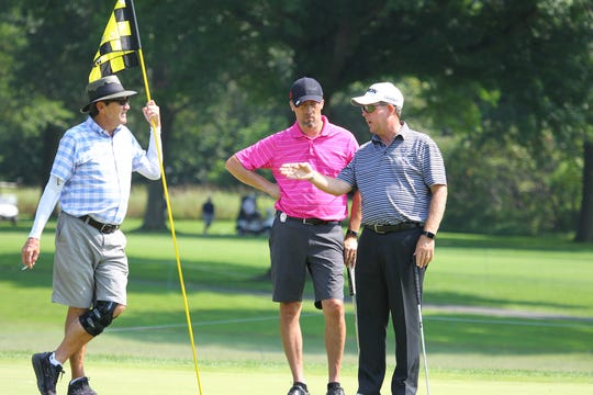 Glen Day gives Jeff Tiderencel some advice on how the green breaks
