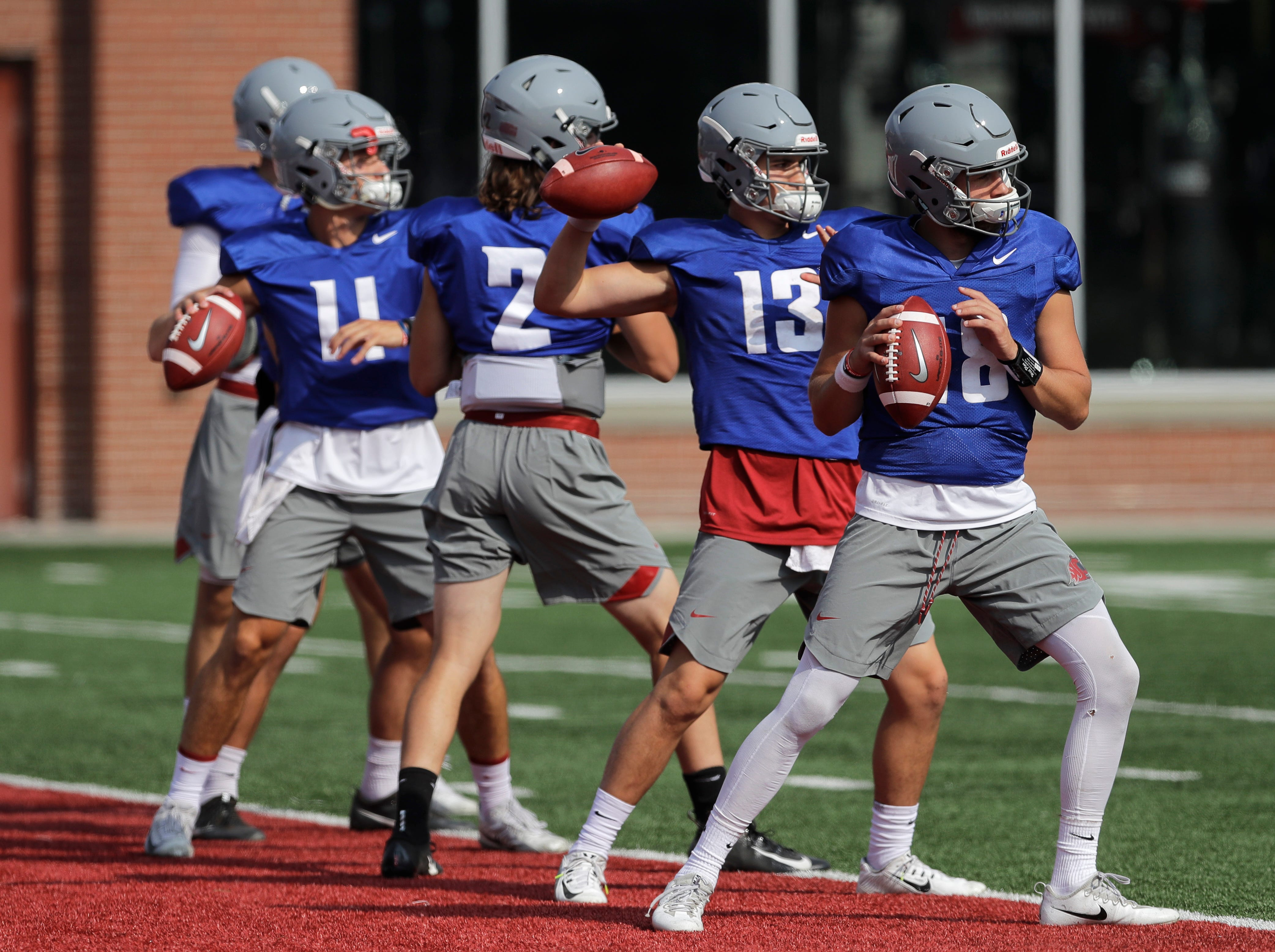 Washington State quarterbacks, including Anthony Gordon, right, and Connor Neville (13) during Thursday's practice. Gordon is one of three quarterbacks competing for the starting job.