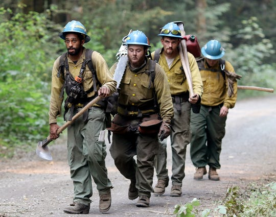 From left, Aaron Reid, Brendon Cunningham, Matt VanDusen and Shane Collins, all with Lost River Fire Management of Klamath Falls, Oregon, return to their vehicle after fighting the Maple Fire in Mason County in summer 2018. Two men have been charged with setting the blaze while trying to take out a bee hive.