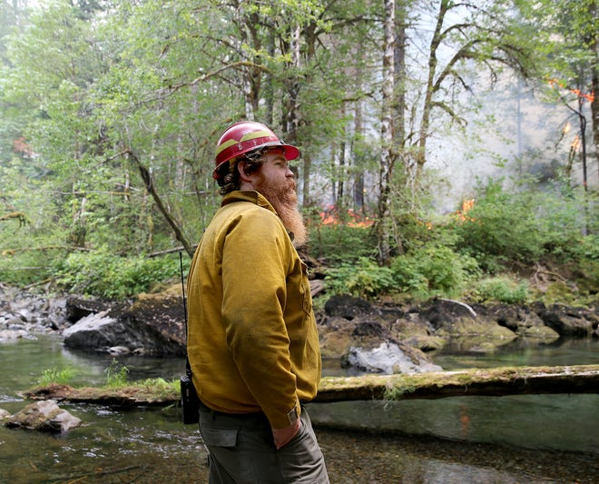 FILE PHOTO - Ben Dean, a U.S. Forest Service firefighter from Quilcene, monitors the Maple Fire.