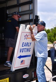 """Brevard County Supervisor of Elections workers unload an """"early voting"""" sign at the Irene H. Canova Park Clubhouse in Indian Harbour Beach in advance of early voting, which runs Aug. 18 through Aug. 25. This is one of eight in-person early voting sites in the county."""
