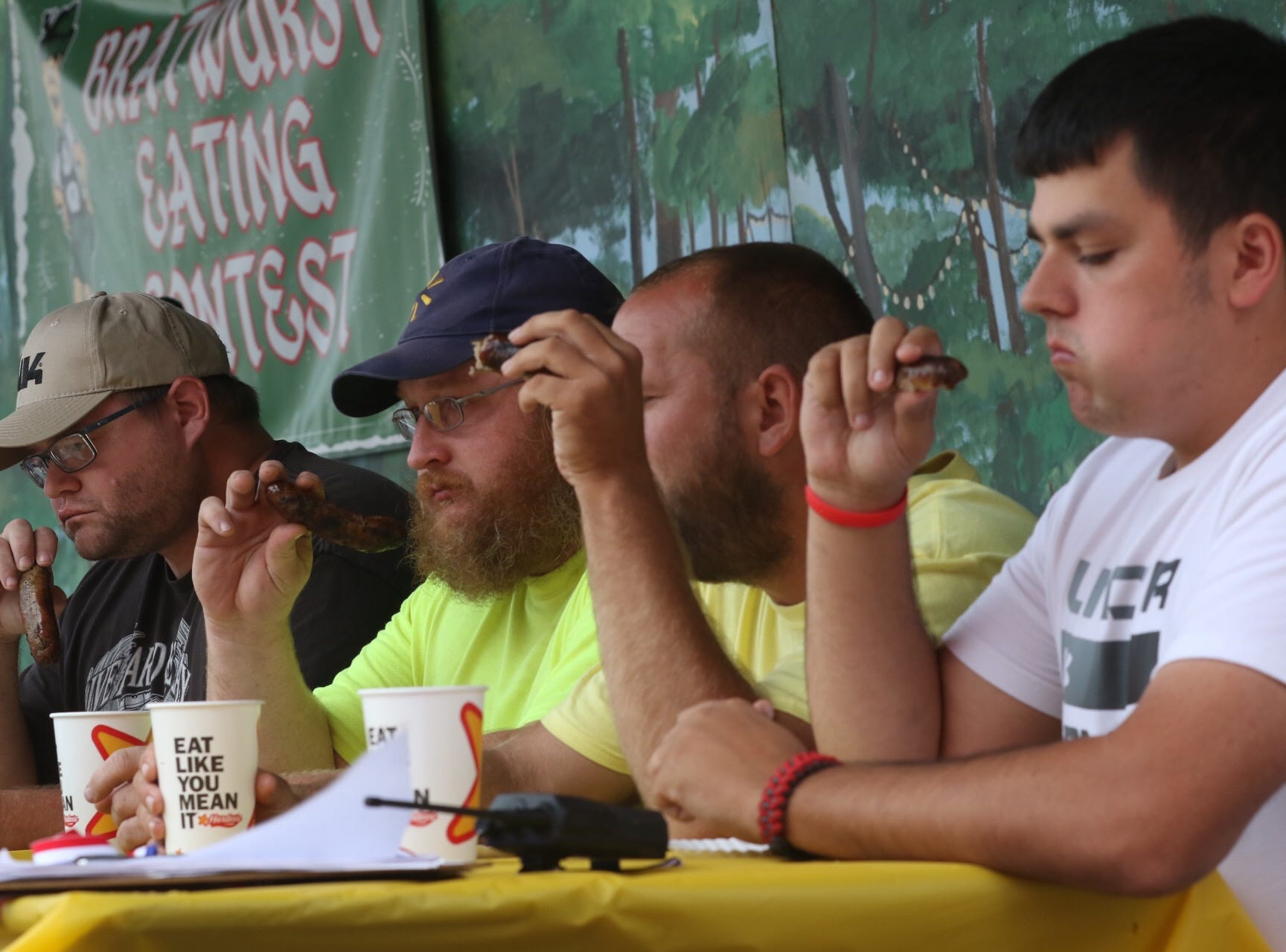 The adult mens group compete in the bratwurst eating contest at Schines Art Park on Thursday afternoon.