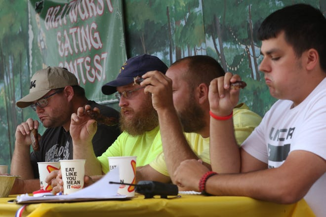 The adult men's group compete in the bratwurst eating contest at Schines Art Park during the 2018 Bucyrus Bratwurst Festival.