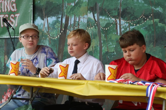 Cassie Willman (left to right), Kevi Kesling, and Don Mills compete in the bratwurst eating contest at Schines Art Park on Thursday afternoon.