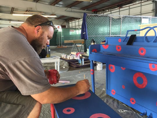 Dennis French of Kittery, Maine, paints a piano bench on Wednesday, Aug. 15, 2018, before Phish's Curveball festival in Watkins Glen, N.Y.