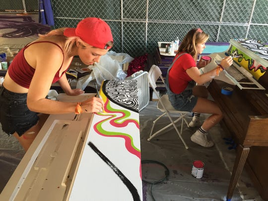 Whitney Olsen, left, and Demi Bechtloff, both of Louisville, Ky., paint pianos on Wednesday, Aug. 15, 2018, before Phish's Curveball festival in Watkins Glen, N.Y.