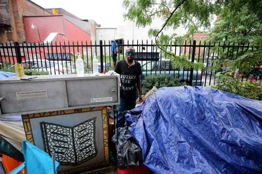 Camp resident Desmond Brown, 41, checks tarps as rain falls,Thursday, Aug. 16, 2018, at the corner of 13th and Republic Streets in Over-the-Rhine. The deadline to clear Cincinnati's homeless camp was extended to Monday. City officials scrapped the previous deadline of noon Thursday so people in the camp would have more time to find housing or shelters.