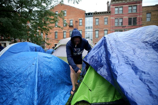 Jessica Barnett, 36, checks on a tarp over her tent, Thursday, Aug. 16, 2018, at the corner of 13th and Republic Streets in Over-the-Rhine. The deadline to clear Cincinnati's homeless camp was extended to Monday. City officials scrapped the previous deadline of noon Thursday so people in the camp would have more time to find housing or shelters.