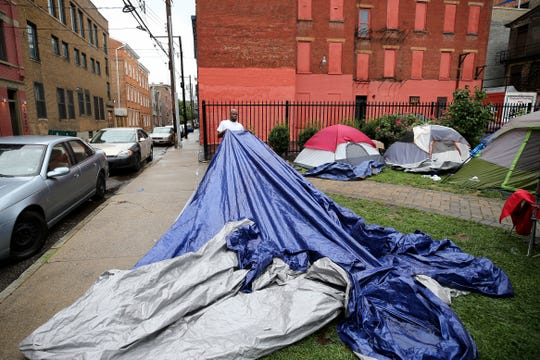 A camp resident who gave his name as Wow Wow, pulls a tarp at the corner of 13th and Republic Streets in Over-the-Rhine was extended, Thursday, Aug. 16, 2018.  City officials scrapped the previous deadline of noon Thursday so people in the camp would have more time to find housing or shelters.