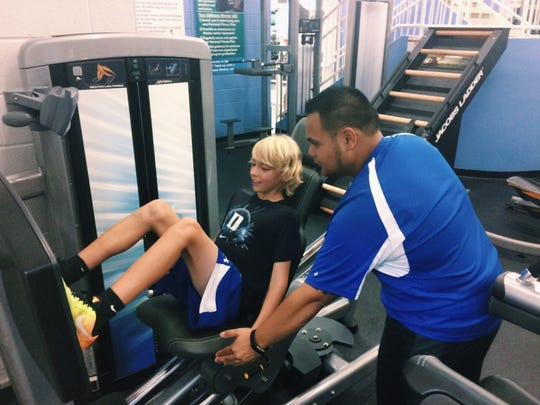 Omar Caponpon, Y Fitness Center Associate, training a 7th grade student on fitness equipment.