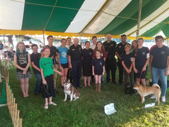 """As part of their community service, the Woof Dog Club raised money via working the kitchen at their dog shows and """"shake-a-can"""" at Tractor Supply and donated $200 to the Country Hills Fire Department to purchase life saving equipment for animals in fires.Check presented by Kate McHale. Photo was taken in the Dog Show Tent at the Somerset County 4-H Fair."""