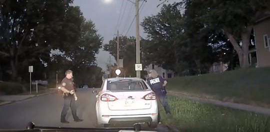 Des Moines police officers Kyle Thies, left, and Natalie Heinemann approach a vehicle during a traffic stop near Union Park on Sunday, July 15, 2018. This dashboard camera recording was released by Iowa Citizens for Community Improvement.