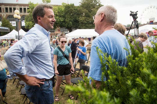 Steve Bullock, Governor of Montana, talks with people who came to hear him speak at the Des Moines Register Political Soapbox on Thursday, Aug. 16, 2018, at the Iowa State Fair.
