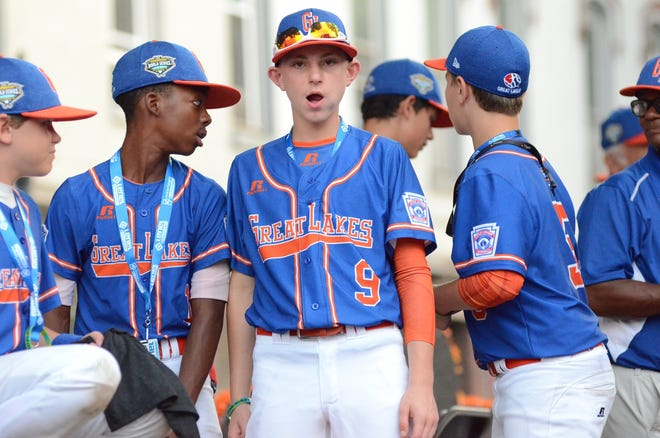 Grosse Pointe Woods-Shores' Reggie Sharpe, Cameron Schafer, and Jake Martin stand on the team float during Wednesday's Grand Slam Parade in downtown Williamsport, Pa.. The event kicked off the festivities for the 72nd  Little League World Series.