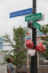 Montez Miller looks up at balloons she placed on Aretha Franklin Way at Brush and Madison streets in downtown Detroit in honor of Aretha Franklin, the Queen of Soul, who died today, Thursday, August 16 2018.
