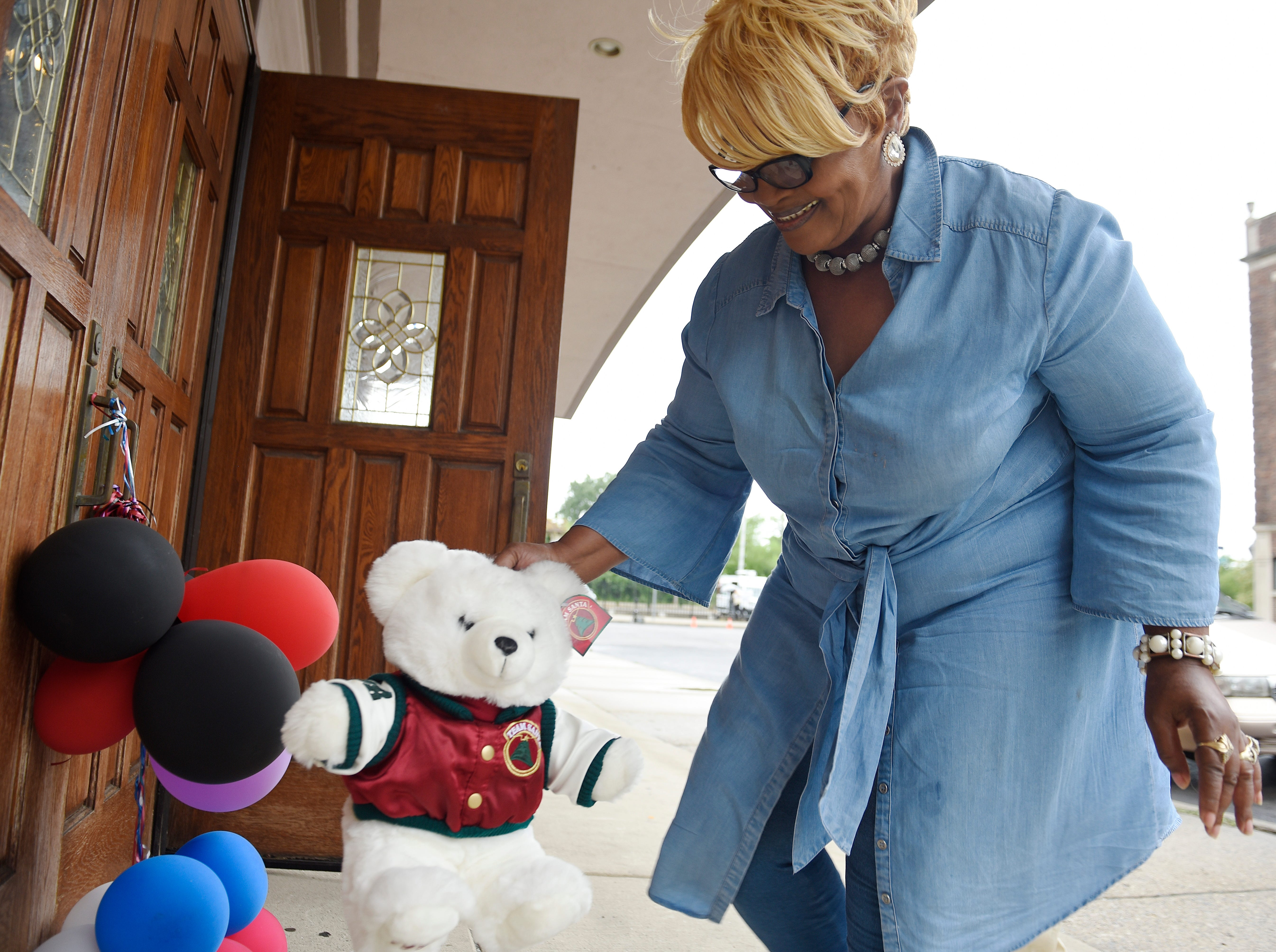 Sennettra Allen, 66, of Detroit pays her respects by leaving a teddy bear at a makeshift memorial outside New Bethel Baptist Church in Detroit, Aug. 16, 2018.