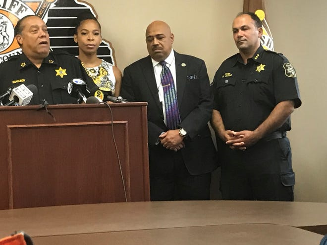 Wayne County Sheriff Benny Napoleon, left, speaks August 16, 2018 about the arrest of a driver accused of driving into and killing Wayne County Sheriff's Sgt. Lee Smith on August 15.