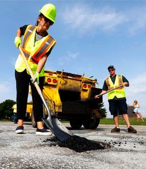 Michigan Democratic gubernatorial candidate Gretchen Whitmer fills a pothole during a campaign event in Southfield, Mich., Monday, Aug. 6, 2018. (AP Photo/Paul Sancya)