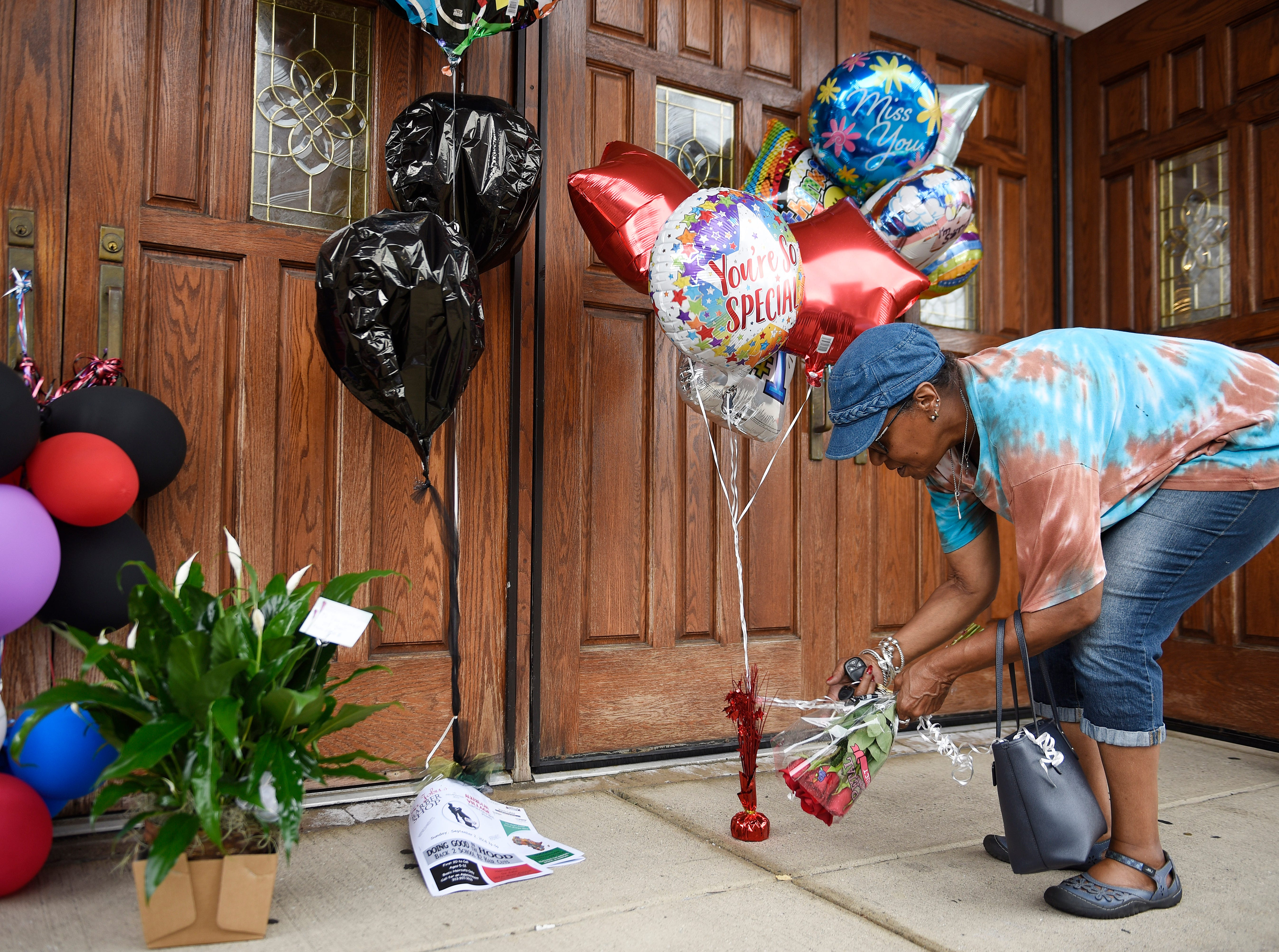 Cecily McClellan, 66, of Detroit leaves flowers at an impromptu Aretha Franklin memorial site at New Bethel Baptist Church, in Detroit.
