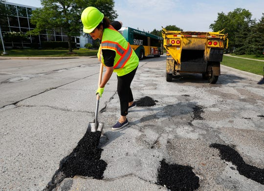 Michigan Democratic gubernatorial candidate Gretchen Whitmer fills a pothole Monday, Aug. 6, 2018 during a campaign event in Southfield, Mich.
