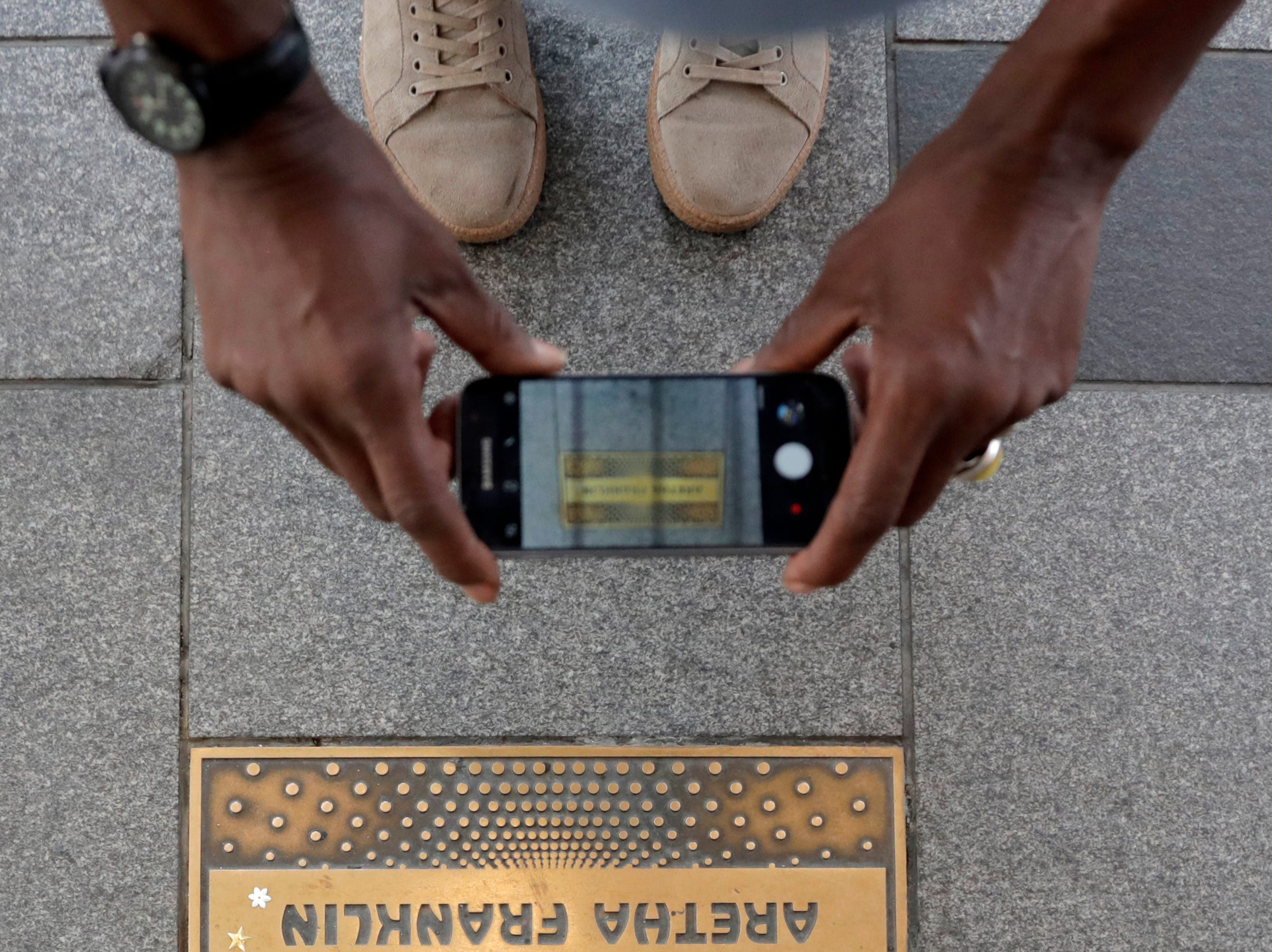 A man photographs the nameplate of singer Aretha Franklin outside the Apollo Theater, Thursday, Aug. 16, 2018, in the Harlem section of New York. Franklin died in her home in Detroit at age 76 from pancreatic cancer.