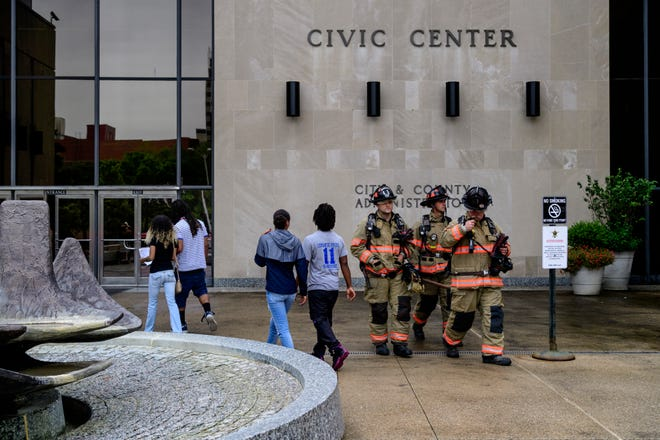 People walk into the Civic Center, crossing paths with Evansville firefighters, after briefly being evacuated from the building due to a possible gas leak, Thursday afternoon. Investigators found the reported smell was cleaning chemicals, not natural gas, and allowed everyone to go back inside the building within 15 minutes of the initial evacuation.