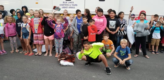 Ottawa County area children wait outside the charter bus used for the Salvation Army summer camp trip.