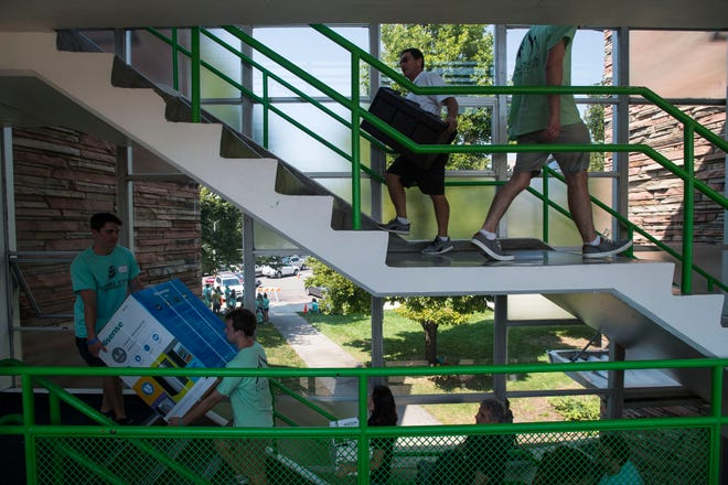 Students and parents carry belongings up a flight of stairs in Allison Hall during student move-ins on Thursday, Aug. 16, 2018, on campus at Colorado State University in Fort Collins, Colo.
