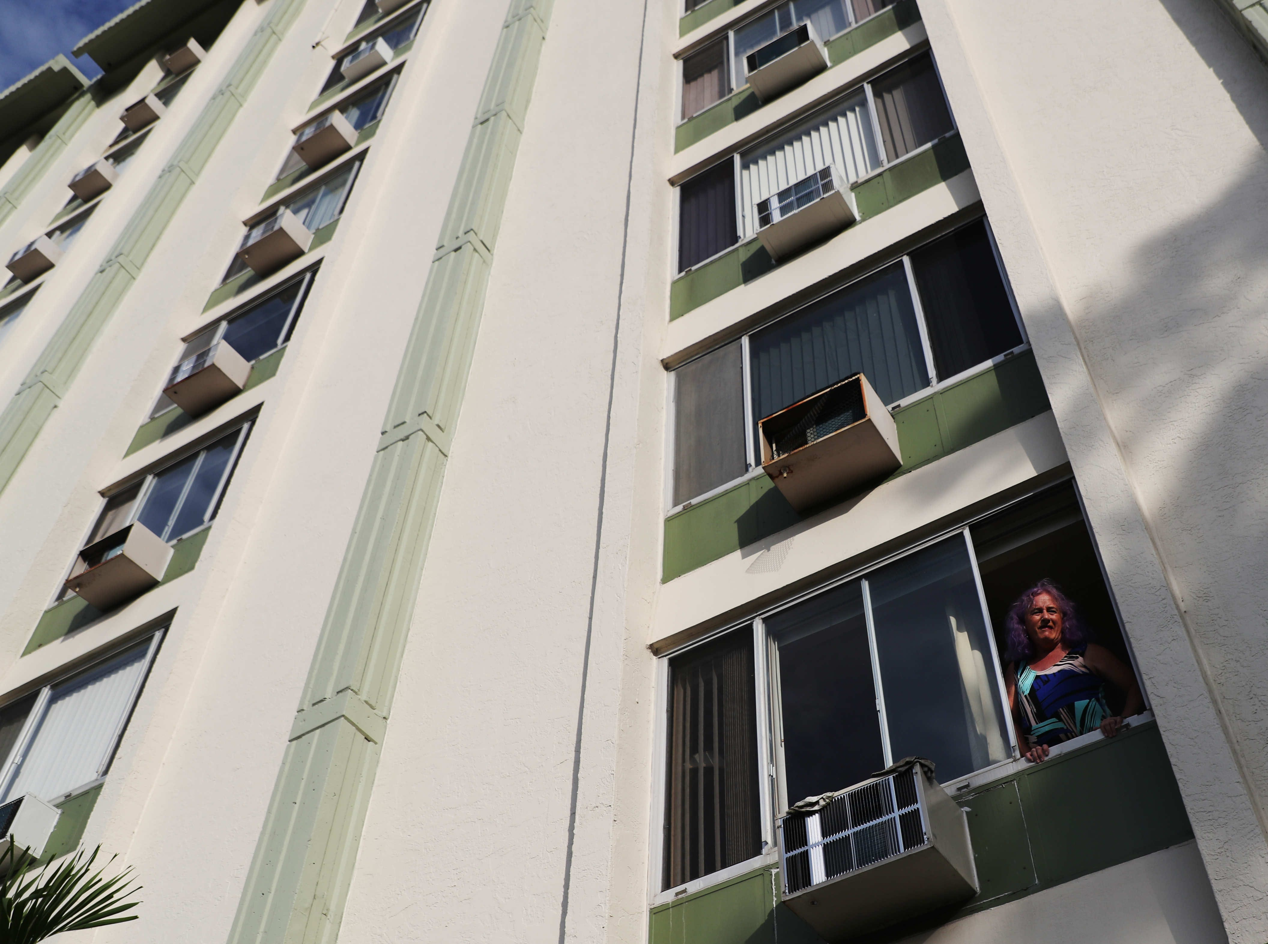 Jenna Satterfield, 62, poses in the window of her downtown Fort Myers apartment. Satterfield, a transgender  woman alternated between unemployment and homelessness due in part to discrimination, she says.
