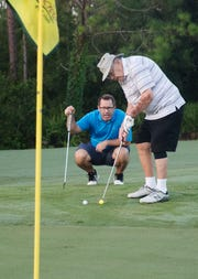 Lewis Keister,92, of Fort Myers lines up a putt while his grandson, J.D. Keister gives advice at Old Corkscrew Golf Club on Thursday morning.