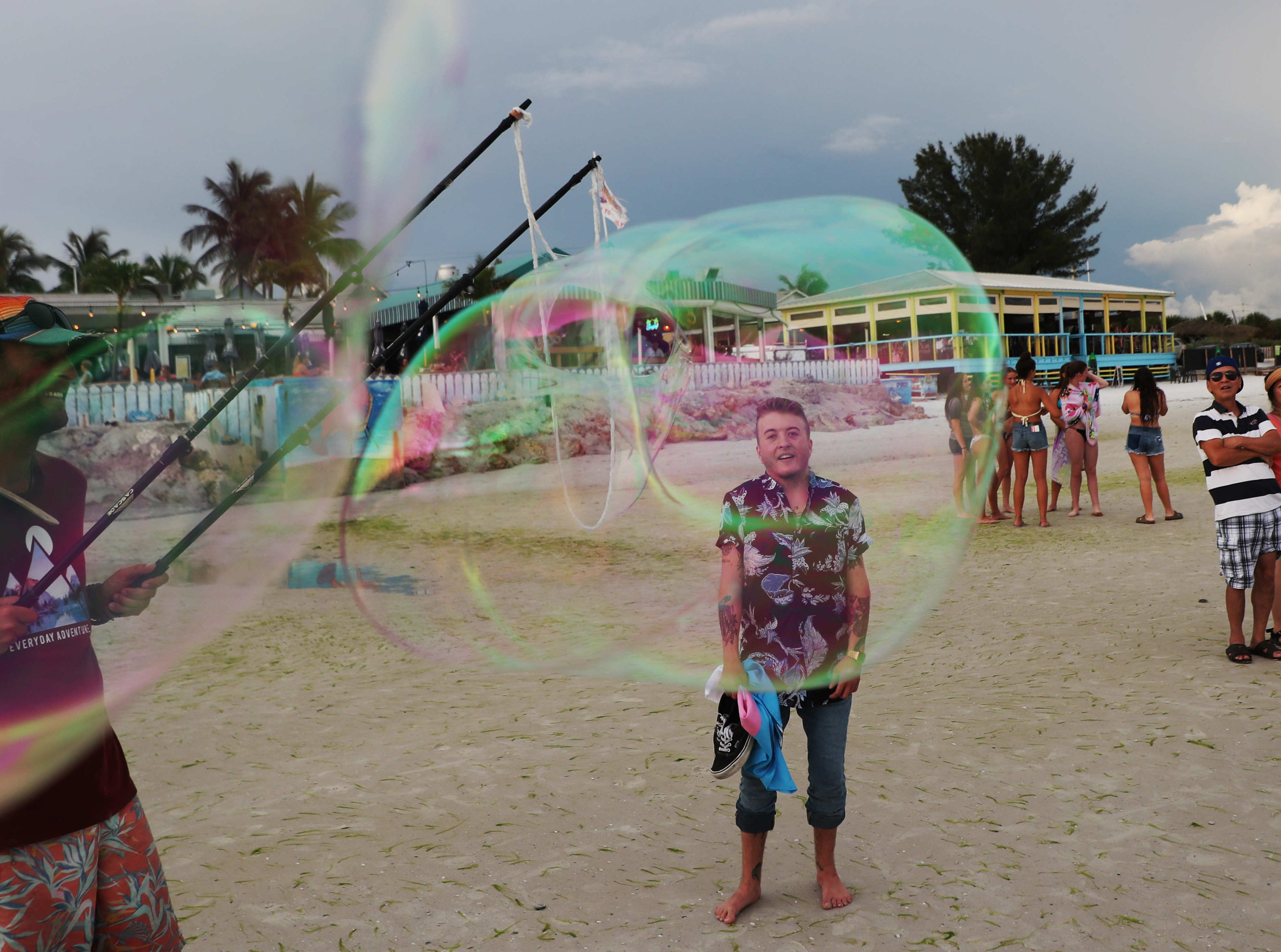 Kasey Fraize watches as Paul Saccone blows giant bubbles for the pleasure of Fort Myers Beach goers on a recent evening. Fraize struggled through middle and high school with his female identity, at 15 he knew he wanted to transition but waited until college to avoid the hassles of parents, teachers and peers.