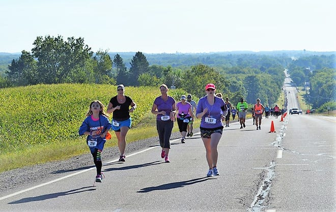 Runners near the crest of Suring Hill north of the village in a past races.