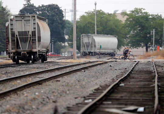 Pedestrians cross the railroad tracks Aug. 16 along Appleton Street in Menasha.