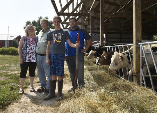 Dale and Karen Cihlar, left, along with their son Ethan Lautenbach, right, and their grandson David Baxter, center, are working to help the Cihlar family farm in Clay Banks, southern Door County,  remain afloat.  Wearing a boot cast for an unrelenting injury, Dale Cihlar will be forced off his feet for rehab following foot surgery. David has been helping to fill the workforce gap.