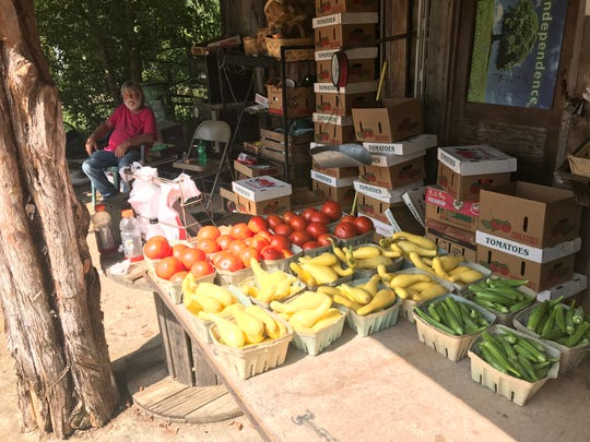 Ralph Perry sits in the shade waiting for a customer at his produce stand in Pumpkintown.