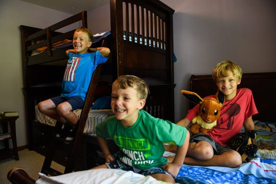 William, Joshua and Sean Reynolds pose for a portrait in their bedroom on Thursday, Aug. 16, 2018.