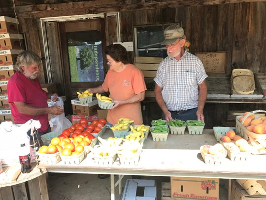 Ralph Perry, left, bags up some produce for Mary and Virgil Lusk at Perry's produce stand in Pumpkintown.