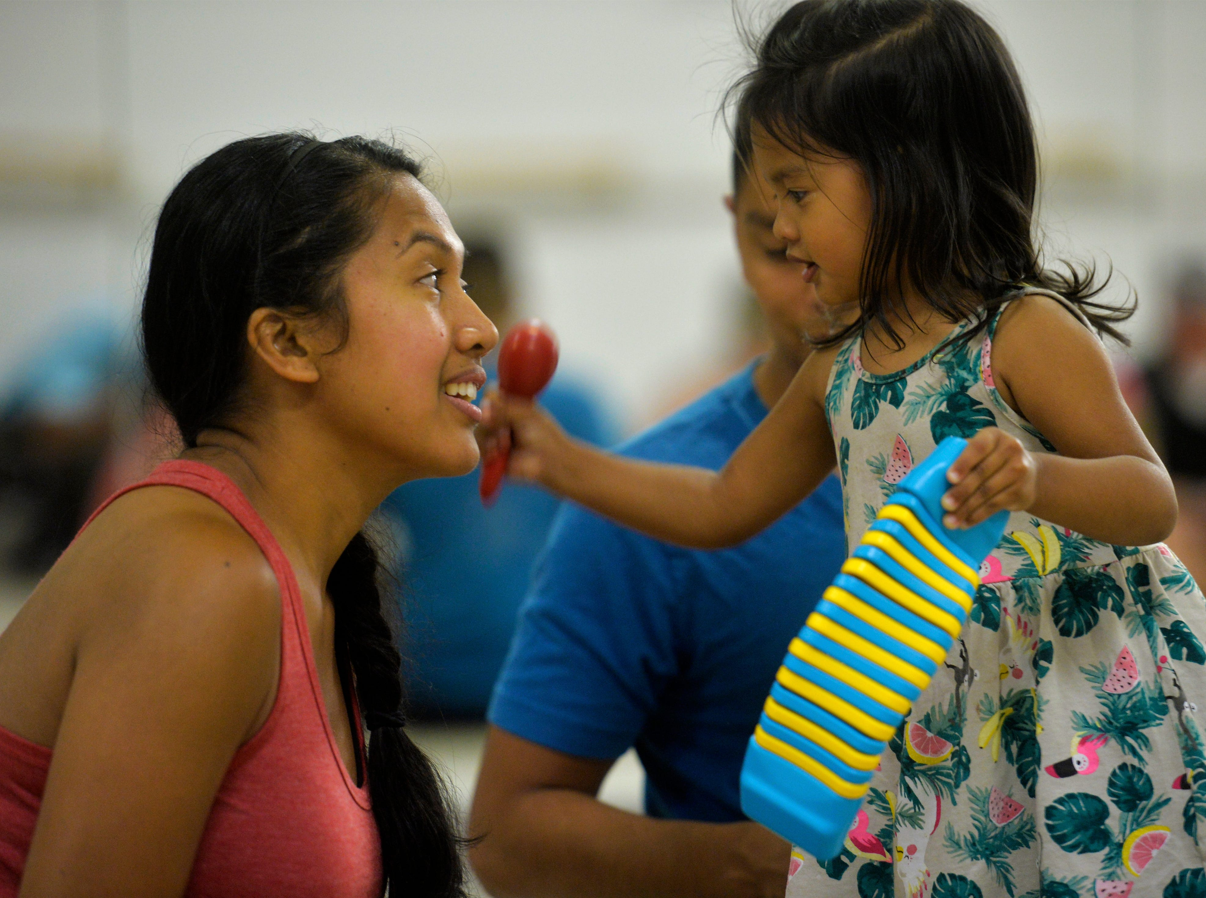 Maebel Zavala, age 2, plays a shaker for her mother, Sheryl, during a music class at the Bass Clef School of Music, recently.