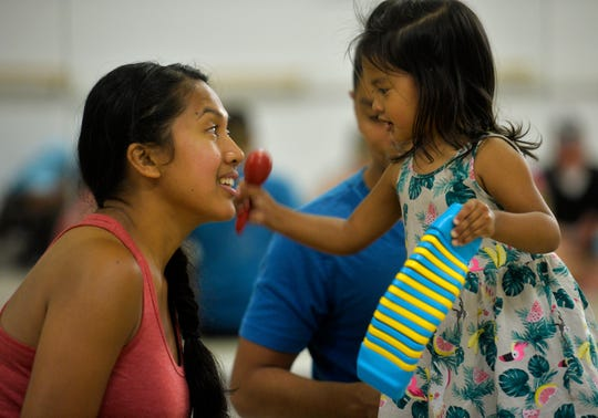 Maebel Zavala, age 2, plays a shaker for her mother, Sheryl, during a music class at the Bass Clef School of Music and Fine Arts.