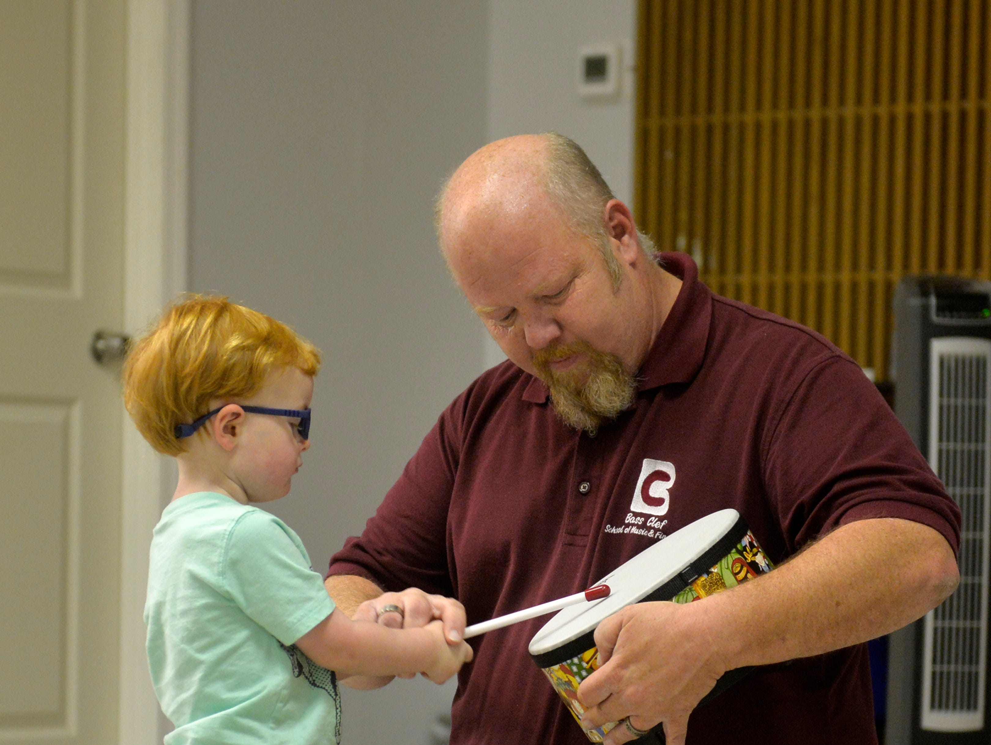 Tim Bass, owner of Bass Clef School of Music, plays a drum with Chace Lee, age 2, during a music class for toddlers and their parents, recently.