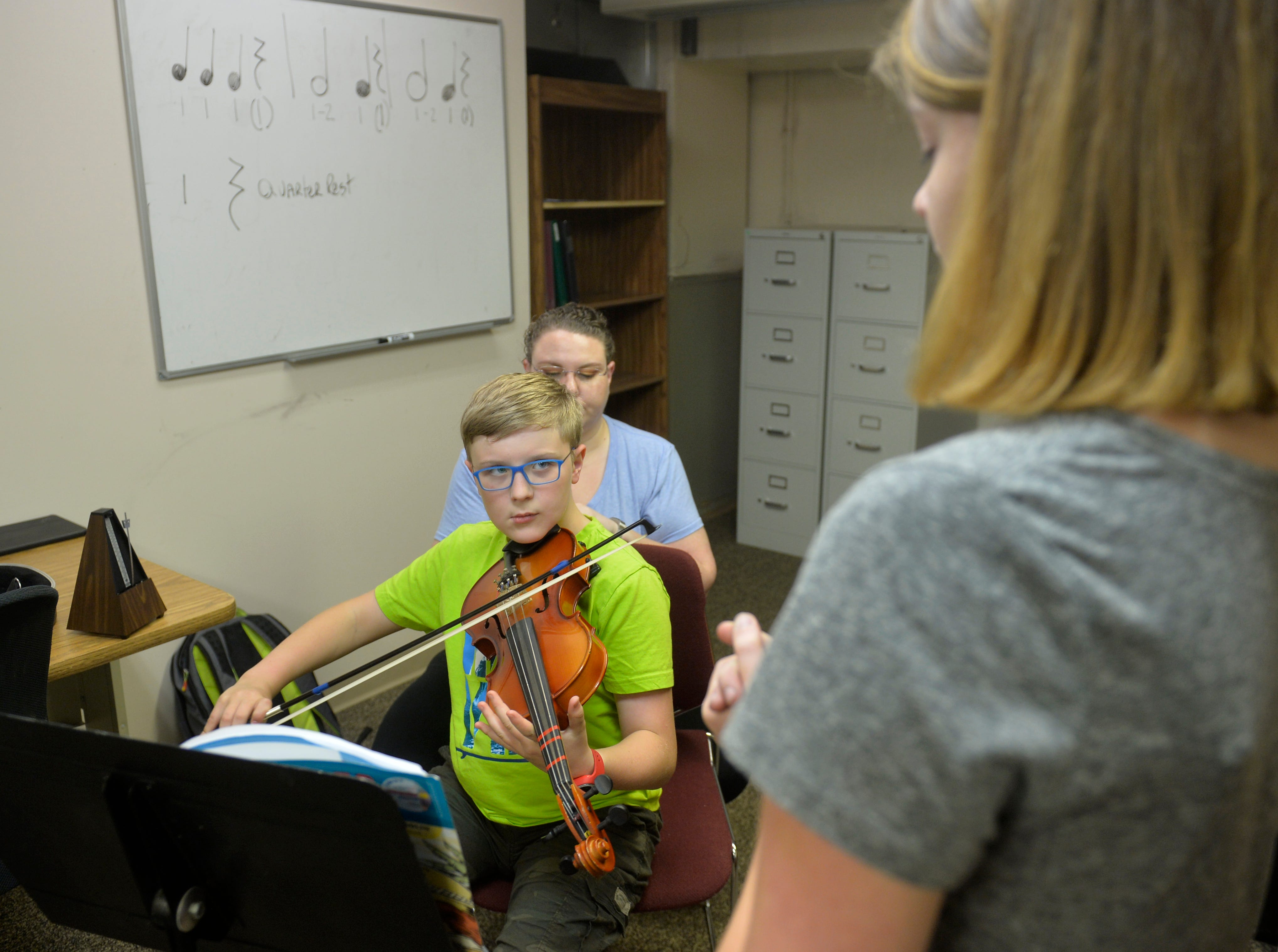 D.J. Loessberg takes a violin lesson from Kailey Dunbar at the Bass Clef School of Music and Fine Arts, recently.