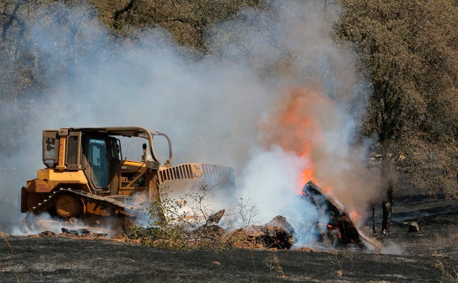 Cal Fire bulldozer 2341 pushes through a mound of burning vegetation due to a wildfire in Grass Valley, Calif.