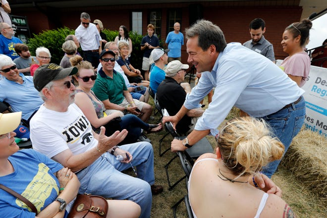 Montana Gov. Steve Bullock talks with Richard Juel, of Pittsburgh, Penn., left, during a visit to the Iowa State Fair on Thursday in Des Moines.