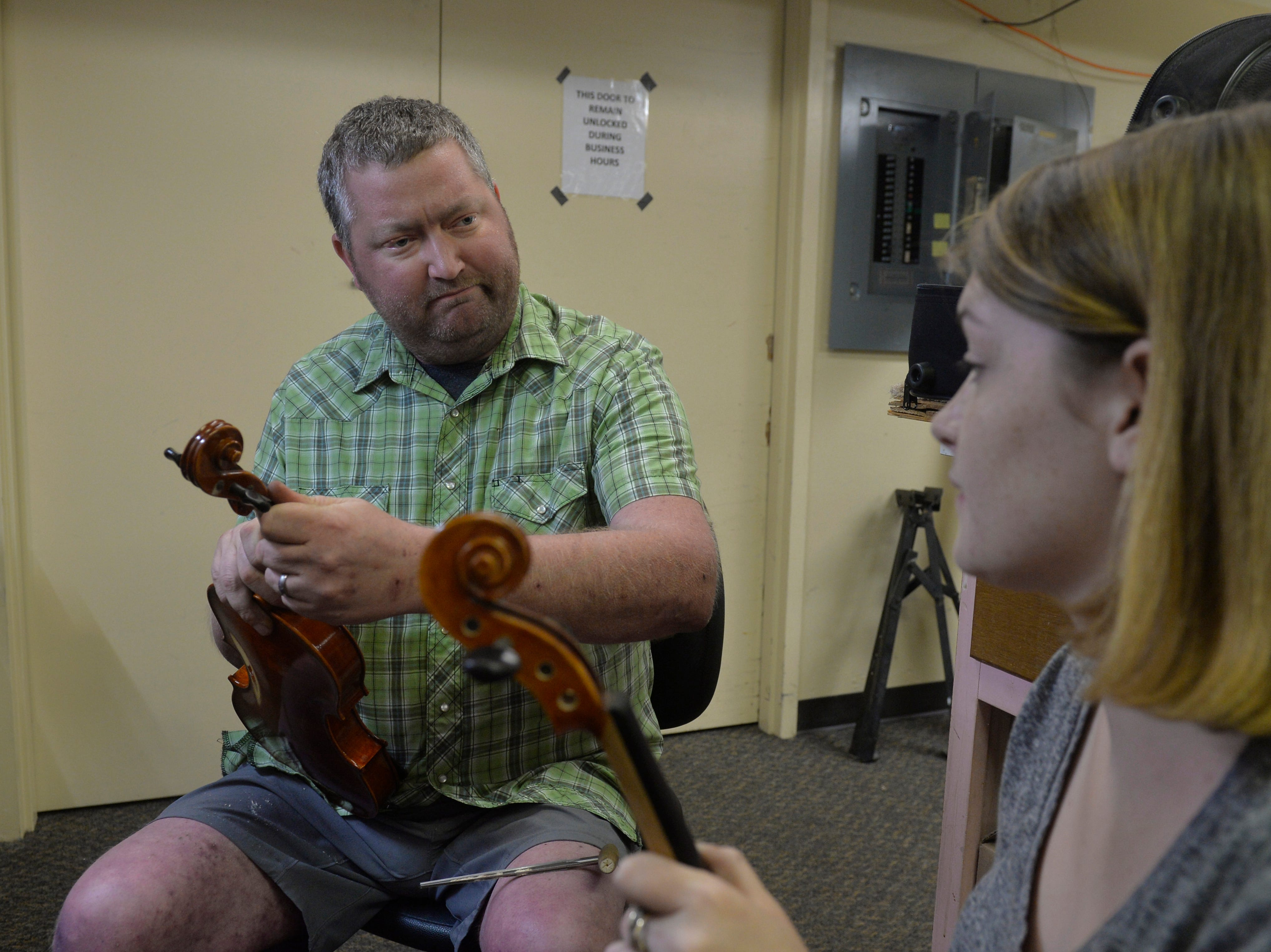 Isaac Calendar teaches Kailey Dunbar about constructing violins that will be used as rentals at the Bass Clef School of Music and Fine Art.